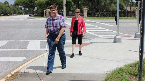 A person with visual disability walks along the sidewalk with a white cane, observed by a mobility instructor who is following a short distance behind.