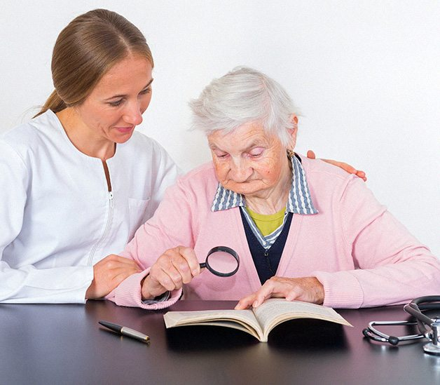 Elderly woman reading with a magnifying glass with the aid of a doctor