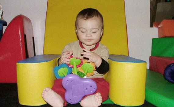A toddler with a visual impairment seated on a yellow play pad with a toy in hand