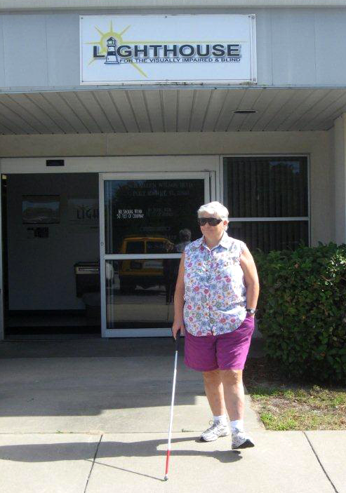 A woman is walking confidently out of the main entrance, using a white cane.