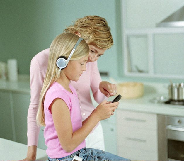 A mother helping visually impaired girl with headphones on navigate an iphone