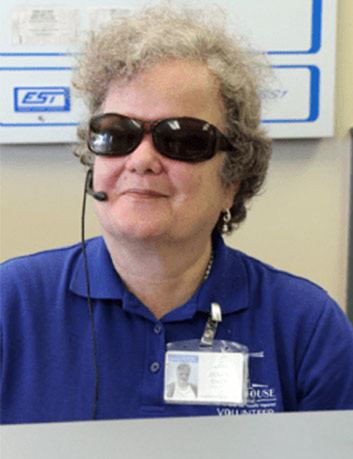 Happy Lighthouse female employee with visual disability talks with individual on her headset phone