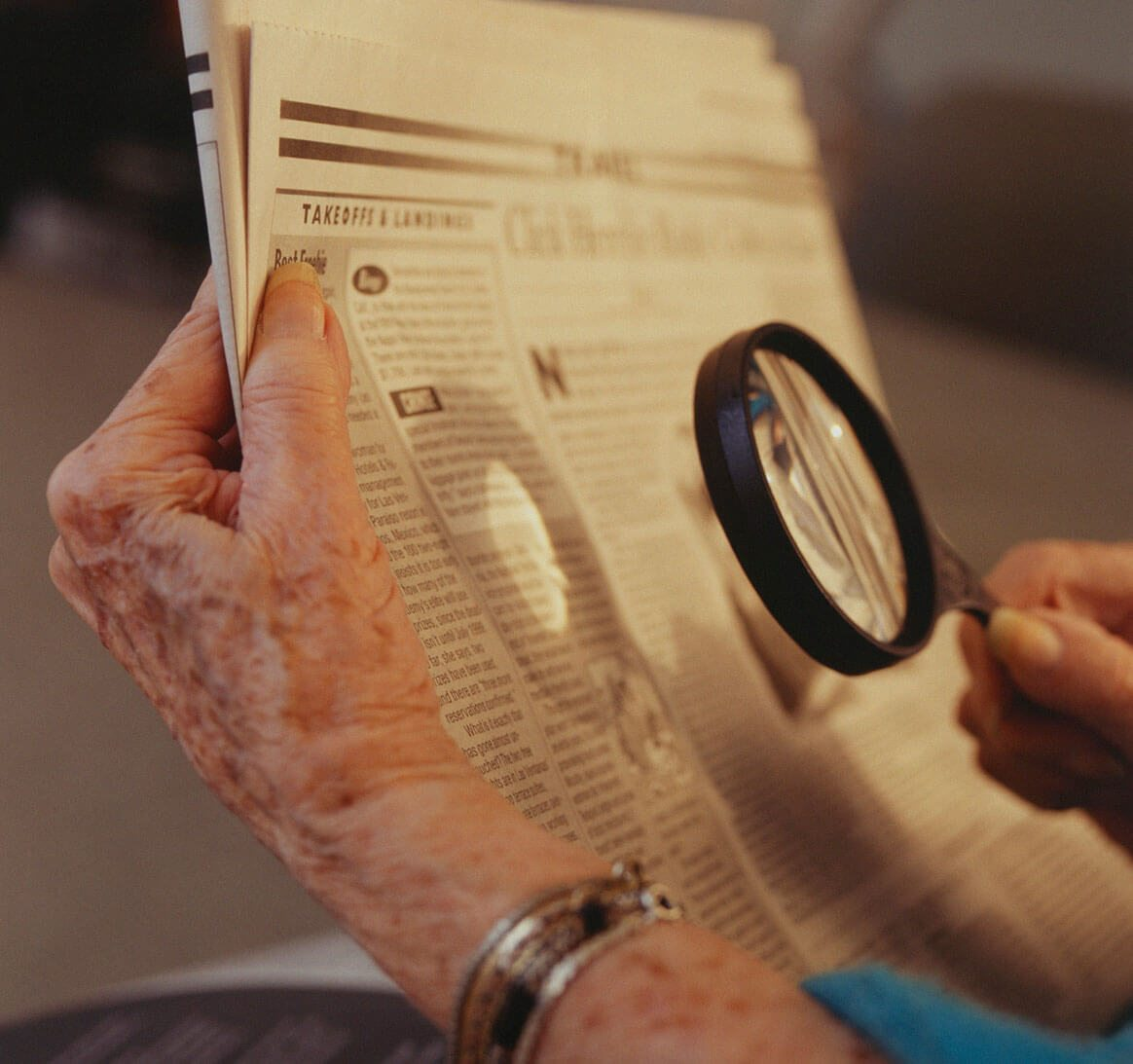 Senior woman sitting on sofa, reading a newspaper with magnifying glass