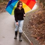 A visually impaired woman holding a large multi-colored umbrella is using her mobility skills to walk safely with a white cane.along a garden path.
