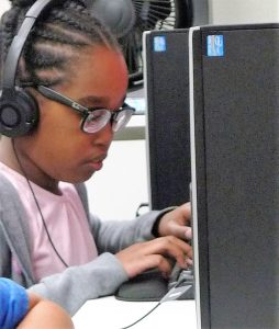 A young visually impaired girl listens to the computer to practice typing.