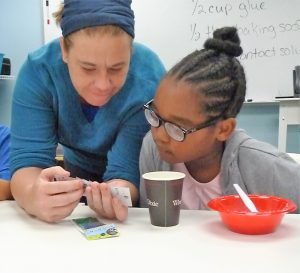 An instructor teaches a visually impaired child to measure and mix a recipe shown on the whiteboard.