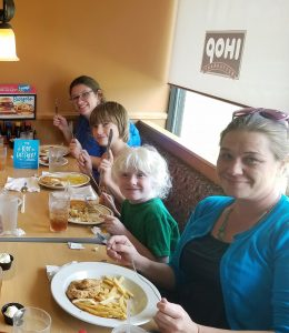 Two Teachers of the Visually Impaired are in a restaurant with children who are visually impaired learning to eat and order food.