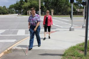 A woman who teaches Orientation and Mobility walks behind a young man who is using a white cane to walk on a sidewalk near a wide intersection.