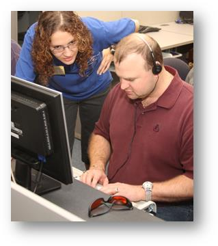 An instructor shows a man who is blind to use a computer. Student is wearing headphones and typing.