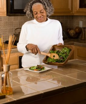 A visually impaired woman is preparing a salad.
