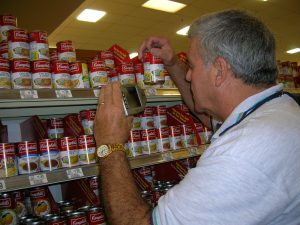 A visually impaired man uses a small electronic magnifier to identify a Campbell's soup can on a grocery shelf.