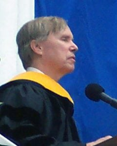 Dr. David Hartman is wearing graduation robes and standing before a microphone on a stage.