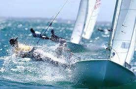A sailboat race with two boats very near each other. Each have one sailor who is leaning completely over the side to balance against the wind. The water is very rough.