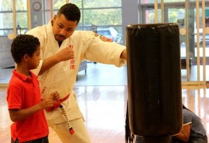 Joshua Espinal is dressed in the traditional white karate gi and demonstrating a punch on a large punching bag to a young boy who is mimicking the move.