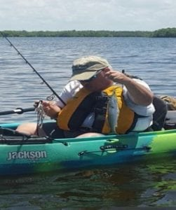 George is in a kayak, wearing a life vest and surrounded by fishing pole and other gear. He is holding up a fish he caught.