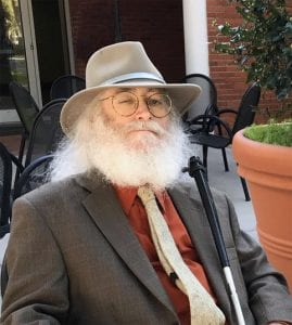 Andrew Meit, seated, wearing a fedora, dark suit jacket, red shirt and beige tie. The upper part of a white cane is visible against his left shoulder. He is seated in a small patio garden.