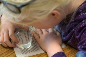 A child uses a magnifier to read