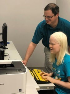 An instructor stands beside a student using a computer with a keyboard with yellow keys and black large print letters.