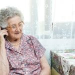 Older woman seated by her lace-curtained window, speaking on the phone with a sweet little smile on her face.